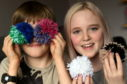 Stonehaven brother and sister Bert and Maddy Mearns, have raised over £1,000 for Cancer Research UK after making pom poms and selling them for donations in the village.