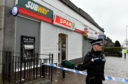 Police attend the scene of a robbery at the Spar on Clifton Road last month.