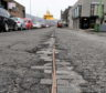 The tarmac has broken up on Commerce Street, Aberdeen, revealing the old cobbles and cables underneath.