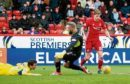 Ryan Christie, right, rounds Saints keeper Alan Mannus and leaves former Don Joe Shaughnessy floored before scoring