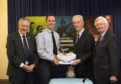 John Cowe, chairman of  Moray Economic Partnership, Wing Commander Matt Hoare, acting Station Commander of RAF Lossiemouth, Jim Walker, joint managing director of Walkers shortbread, and Lt Col Grenville Johnston, Lord Lieutenant of Moray, share cake at the ceremony.