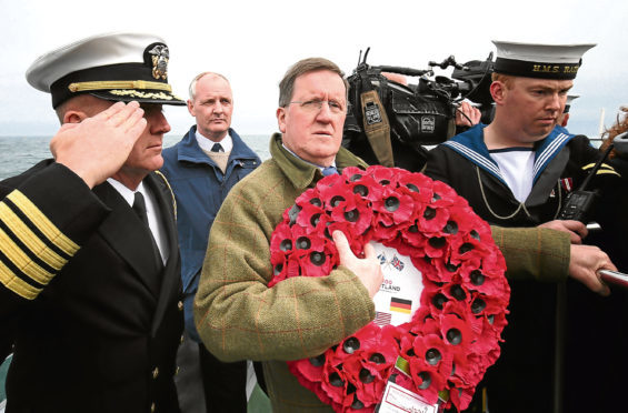 Lord George Robertson holds a wreath prior to throwing it in the sea close to the wreck of SS Tuscania which sank in 1918 off the coast of Islay.
