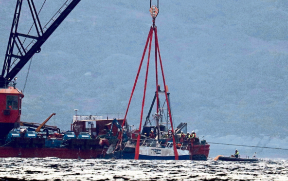 The Nancy Glen trawler sits alongside a barge on Loch Fyne following its recovery after sinking on January 18, with two men lost