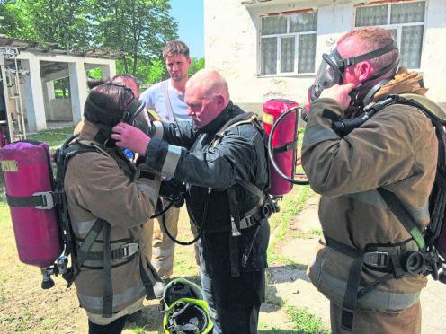 Volunteer Rab Forsyth demonstrates the use of breathing apparatus in Nisporeni, Moldova.