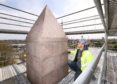 Barratt Homes worker Connor Higgins added the finishing touches to the top of the obelisk.