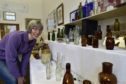 Doric Neuk founder Hannah Pennig inspects the bottles