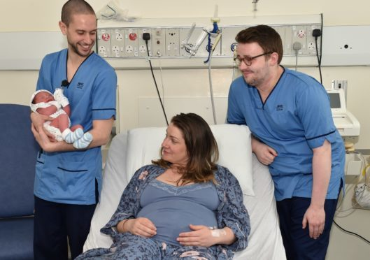 ARI has two male midwifes. They want to show it isn't just a job for women. Iain Macaulay (wearing glasses) and Miguel Angel Del Fresno with Baby Dominic and mum Veronica Tomozei. Picture by COLIN RENNIE May 2, 2018.