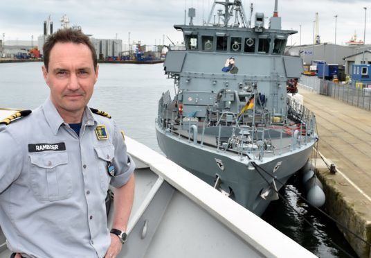 Commander Peter Ramboer (Belgian Navy) at Aberdeen Harbour with the German Navy's Frankenthal-class mine hunter FGS Bad Bevensen in the background.