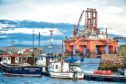 Small boats in Cromarty Harbour are dwarfed by the West Phoenix oil rig situated in the Cromarty Firth