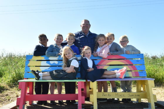 Mike Duncan with children at the new bench on the Cove Woodland Walk.
