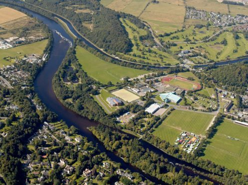 Bught Park, with its shinty pitches occupies the right foreground in this view, with the city's main leisure complex beyond.  This includes Queen's Park Sports Ground and Athletics Stadium; the ice rink, swimming pool and leisure centre, and the floral hall and botanic gardens. Torvean Golf Course lies beyond the Caledonian Canal in upper centre and right. A new road has proposed, which will link the Dores Road to the west (left) of the River Ness with the A82 Inverness to Fort William Road, on the western side of the River Ness and Caledonian Canal and this can be seen running though Torvean Golf Course in this view. The new road will cross the River Ness via a new bridge at the weir in the upper left of this view, and the Caledonian Canal via a swing bridge, which will open to permit traffic alond the busy canal.