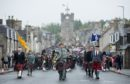 The massed pipes and drums marched from Dufftown's clock tower to the town's Highland Games.