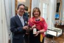 Fiona Hyslop, holding a bottle of Ben Nevis with Nikka Whisky master blender Tadashi Sakuma.