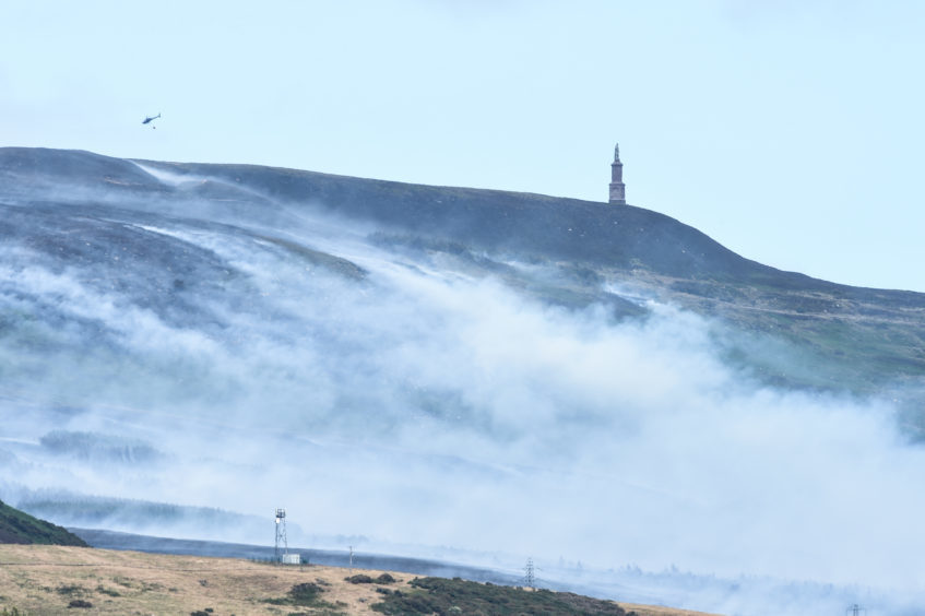 Picture by JASON HEDGES   Pictures show large areas of smoke and fire crews fighting a gorse fire at Ben Bhraggie, near the Duke of Sutherland Statue.