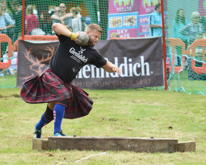 Picture by JASON HEDGES   Pictures show the sporting events of Tomintoul, 2018 Highland Games.  Picture:   Scott Rider giving it his all on the Heavy Stone.