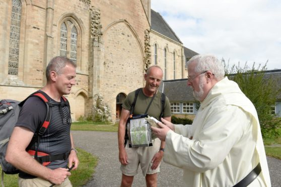 Pilgrims Andy Wallis (left) and Alistair Monkman (right) are greeted at Pluscarden Abbey last night by Abbot Anselm