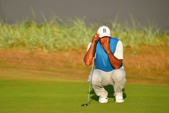 Tiger Woods lines up a putt on the 18th green during the first round of the 147th Open.