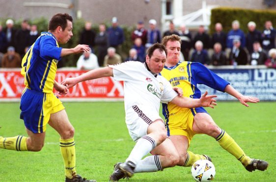 Alan Hercher (centre, in white) in action for Clach.
