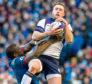 Scotland's Stuart Hogg keeps possession under pressure against France in February.