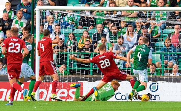 Aberdeen's Tommie Hoban forces the opener home, as Hibernian's Adam Bogdan dives in vain.