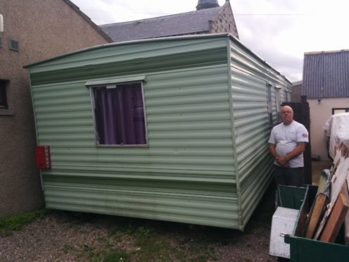 Mr Knowles stands next to the caravan between his home and the restaurant