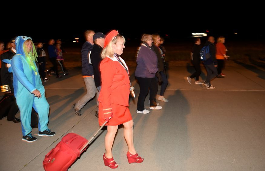 Walkers and runners complete a three-mile course round the main runway of the airport.