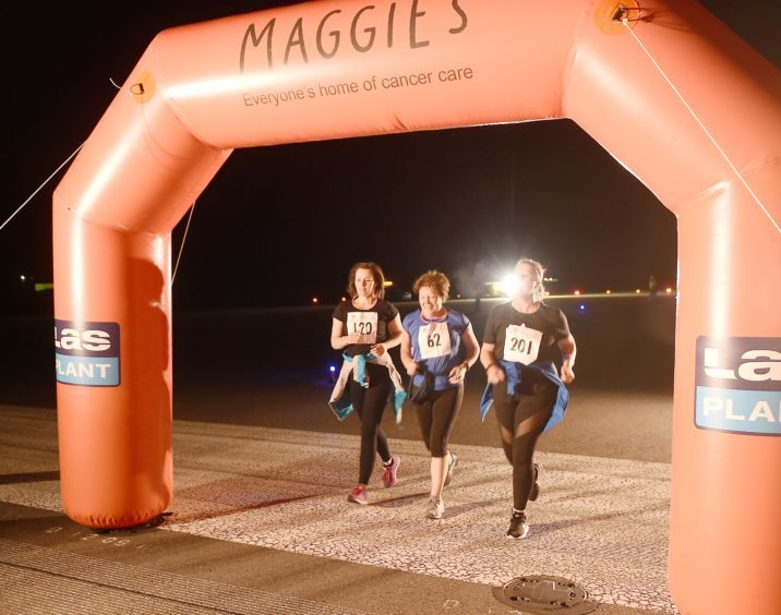 Runners and walkers cross the finishing line on the main runway.