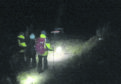 A small team of CMRT guiding the pair of lost walkers off the Cairngorm plateau.