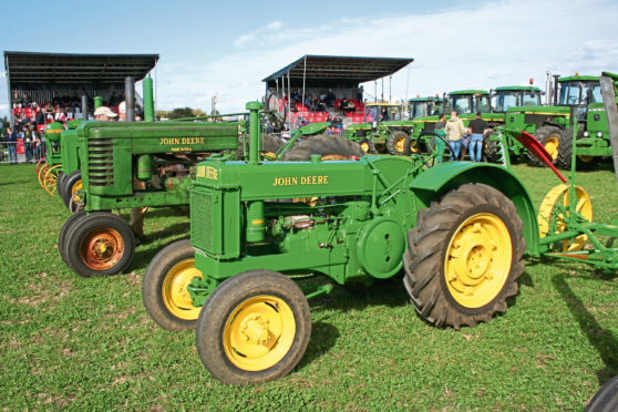 An unstyled John Deere BR sits alongside a Henry Dreyfuss styled John Deere Model A at the UK John Deere at 50 event at Langar in Nottinghamshire in 2016.