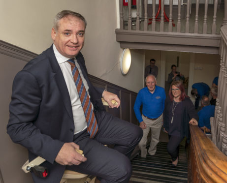 MSP Richard Lochhead uses the seat lift to negotiate the stairs watched by David Thow, Chairman of Fochabers Mens Shed and Morven Smith, Head of Community Investment SSE Plc.