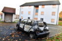 A burnt out renault car, at a block of boarded up flats at Marchburn, Northfield.     Picture by Kami Thomson    26-101-7