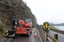 Engineers work high above the road as a train from Kyle passes works on the A890 Stromeferry bypass.