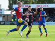 Caley Thistle's Coll Donaldson challenges Don Cowie of Ross County.
