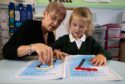 St Peter's Primary School head teacher MandyFeeley and five-year-old pupil Hope Hendry use the maths packs.    Photo by Michael Traill 9 South Road Rhynie Huntly AB54 4GA  Contact numbers Mob07739 38 4792