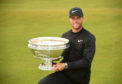 Lucas Bjerregaard of Denmark celebrates with the winners trophy following his victory