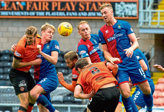 Inverness' Jordan White (R) rises highest, but his header is saved.