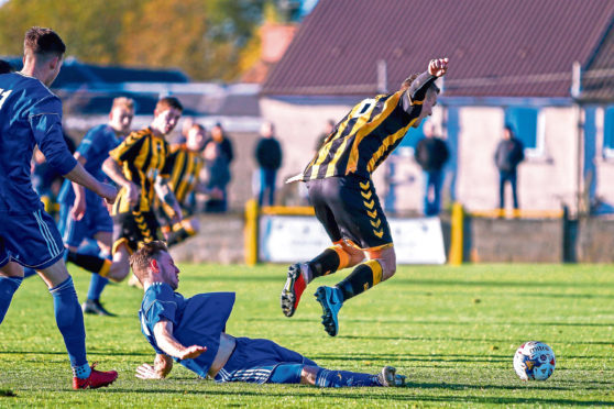 Auchinleck goalscorer Stephen Wilson evades the challenge of a frustrated Mitch Megginson in                                        the tense tie with Cove.