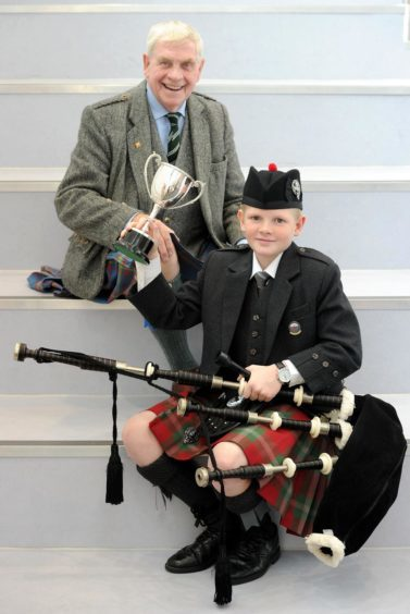 Logie Johnston of Oban High School, winner of the Roderick Ross, Ferintosh, Memorial Trophy for playing a march in the under thirteen age category. Also in the photograph is adjudicator Iain Macfadyen.