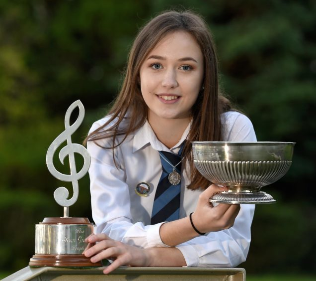 Holly MacLean of Tobermory with the Jean Graham Trophy and the Alexander Hamilton Trophy as aggregate trophies in the solo singing competitions in the 13-15 age group.