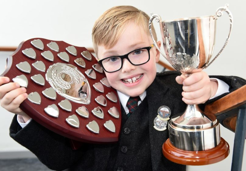 Jonathan Domhnallach of Kilmuir on Skye who celebrates his seventh birthday today (Wed) with the Alasdair Macinnes Memorial Cup for story telling and the Jeff McLaren Memorial Shield for singing a prescribed song in the six years and under age group.