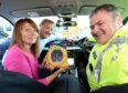Sandra and Gordon McKandie presenting one of six life saving defibrillators to Road Policing Chief Inspector Stewart Mackie. Photo by Sandy McCook