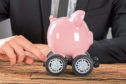 Close-up Of Businessperson Pushing Pink Piggy Bank On Wheels At Desk