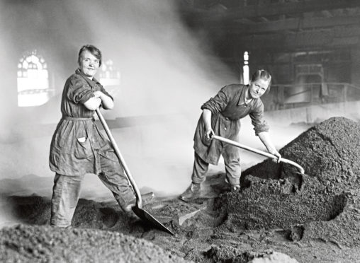 Women war workers feed the charcoal kilns used for purifying sugar at a Scottish refinery.