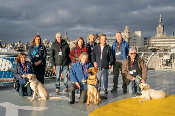 A group photo showing volunteers and their pups, staff from NorthLink Ferries and Puppy Training Supervisor Dave Mackay.  Pups from left to right are Babs (yellow lab retriever cross aged 10 months), Storm (golden retriever cross German shepherd aged 9 months) and Faye (yellow lab retriever cross aged 10 months).