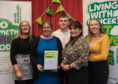 Fiona Lewis, centre left, received the prestigious David MacMillan Award for services to MacMillan Cancer from Isla Dewar, the charity's North of Scotland fundraising manager.