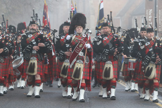 The procession to Cavell Gardens led by the Royal British Legion pipe band.