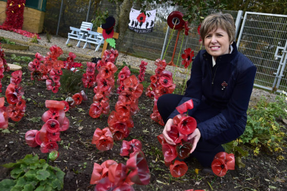 MINTLAW ACADEMY CLASSROOM ASSISTANT HEATHER REID IN THE THE THERAPEUTIC GARDEN BESIDE SOME OF THE POPPY DISPLAY SHE DESIGNED USING PLASTIC BOTTLES.