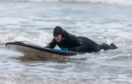 Anne-Marie Walker tries surfing for the first time at the age of 72 at Lossiemouth beech. She is helped by Kev Anderson of the charity, Surfable. Photo by Michael Traill