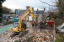 Demolition crews begin knocking down the Tennant Arms.