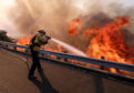 A firefighter battles a fire along the Ronald Reagan (118) Freeway in Simi Valley, California.